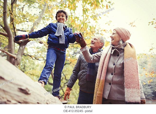 Grandparents walking grandson on log in autumn park