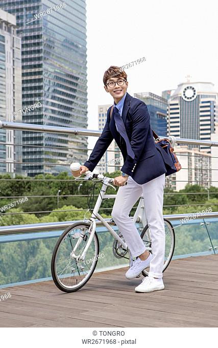 Smiling businessman posing with bicycle