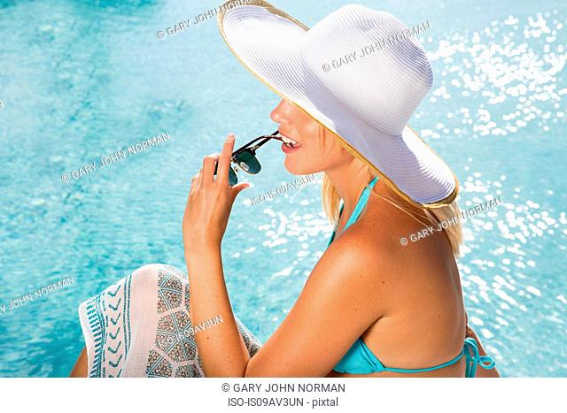High angle side view of young woman wearing sunhat sitting by swimming pool holding sunglasses