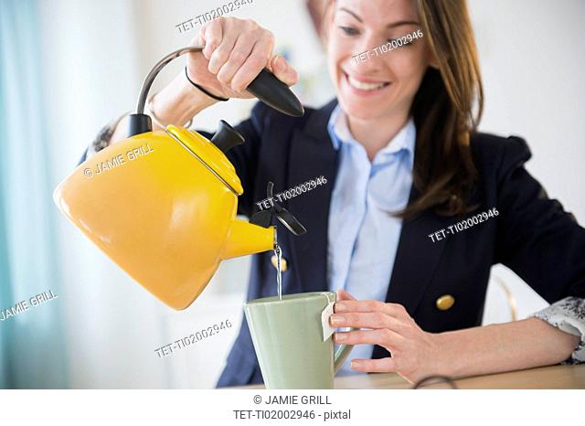 Woman making tea in office