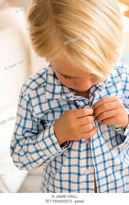 Boy (4-5) buttoning shirt