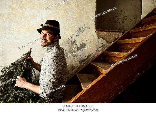 Man with knitted pullover and hat, twigs of evergreens for decoration, stairs, sit, sitting, laugh, half-portrait, side view