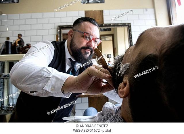 Barber shaving a man using a straight razor