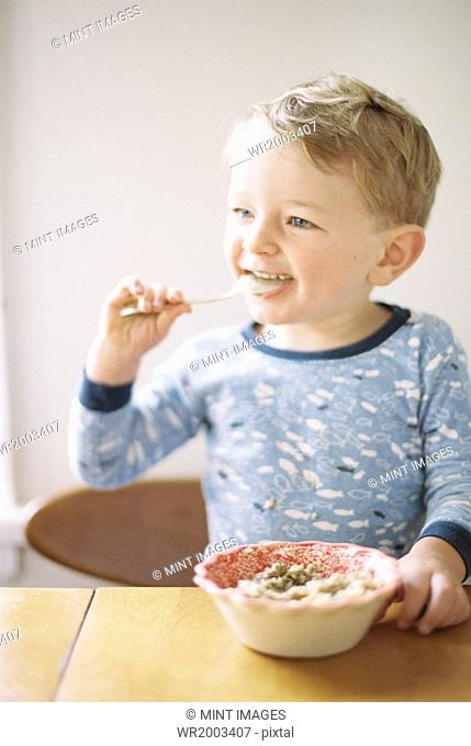 Young boy sitting at a table, eating breakfast from a bowl