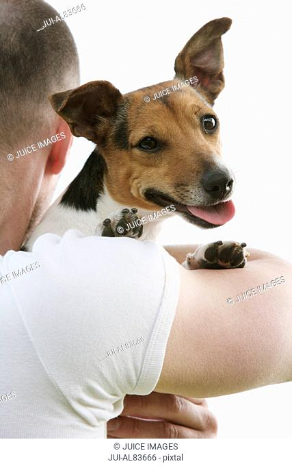Small dog looking over man's shoulder outdoors
