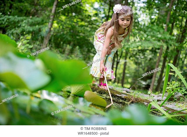 A girl playing at a pond in a forest