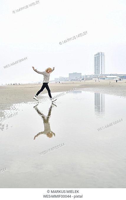 Netherlands, Zandvoort, young woman having fun on the beach