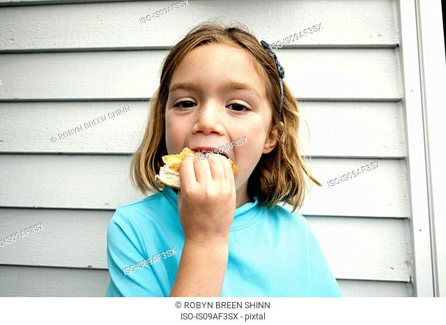 Young girl greedily eating sandwich