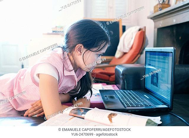 Portrait of little girl at the computer