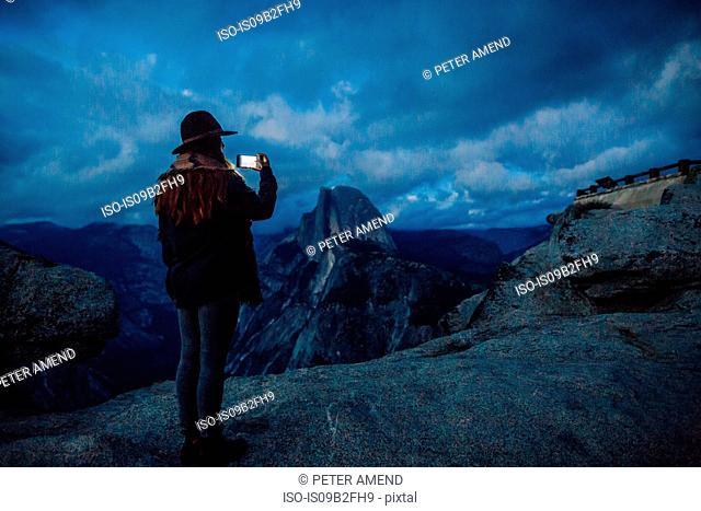 Young woman taking photograph on rock overlooking Yosemite National Park at dusk, California, USA