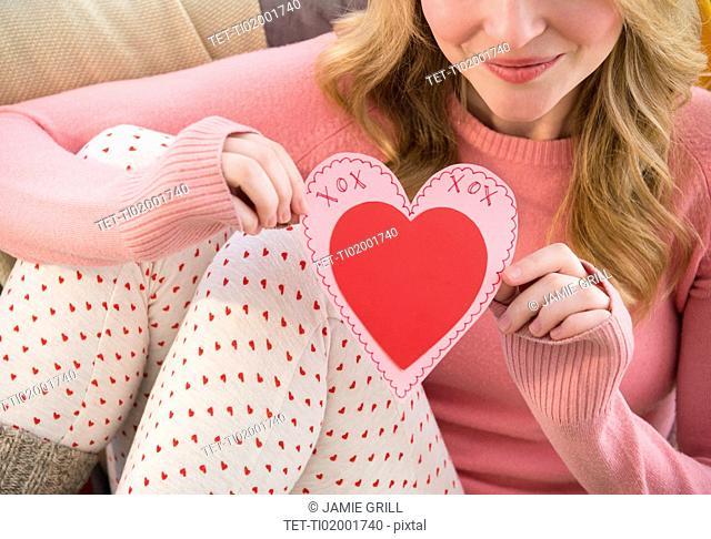 Woman holding heart shape valentine's card