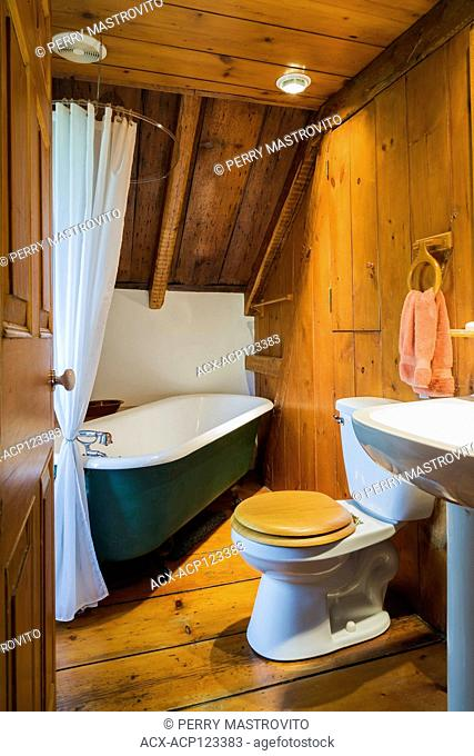 Bathroom with green 1880s claw-foot soaking tub, toilet with wooden seat and pedestal sink on the upstairs floor inside an old circa 1750 Canadiana style...