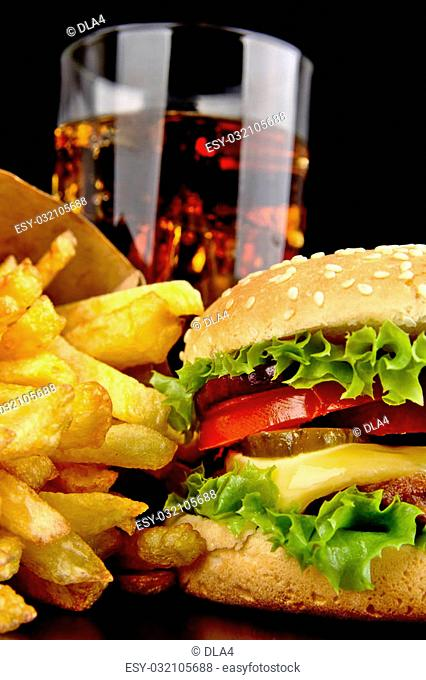 Menu- big cheeseburger with french fries and glass of cola on black