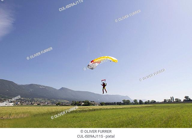 Female skydiver parachuting into field, approaching the landing zone, Grenchen, Berne, Switzerland
