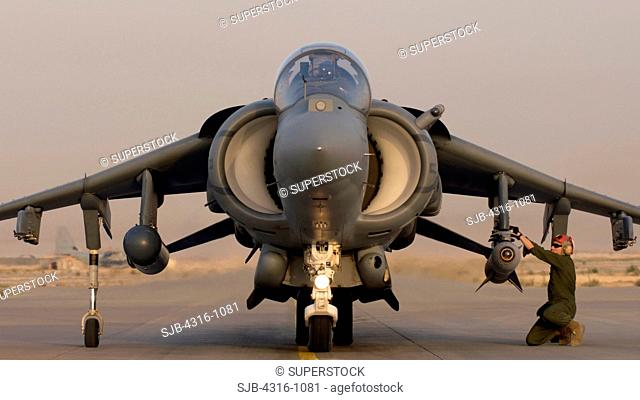 A Ground Crewman Arms Weapons on a US Marine Corps AV-8B Harrier at Al Asad Air Base in the Al Anbar Province of Iraq