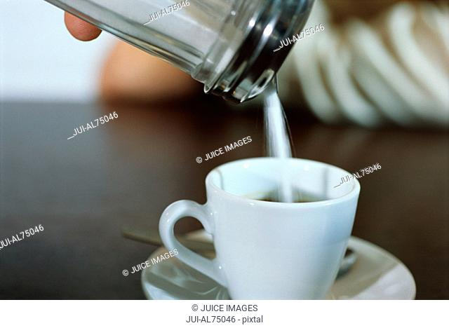 View of a person pouring sugar into coffee