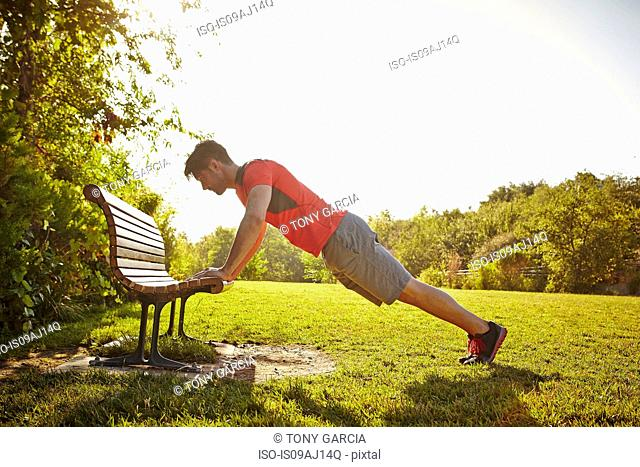Young male runner doing push ups on park bench