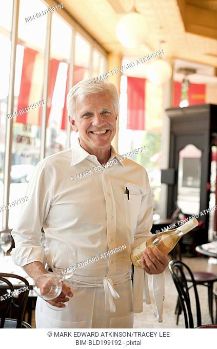 Caucasian waiter holding bottle of white wine