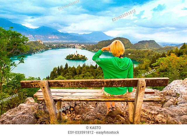 Traveler enjoying the panoramic view of Julian Alps, Lake Bled with St. Marys Church of the Assumption on the small island; Bled, Slovenia, Europe