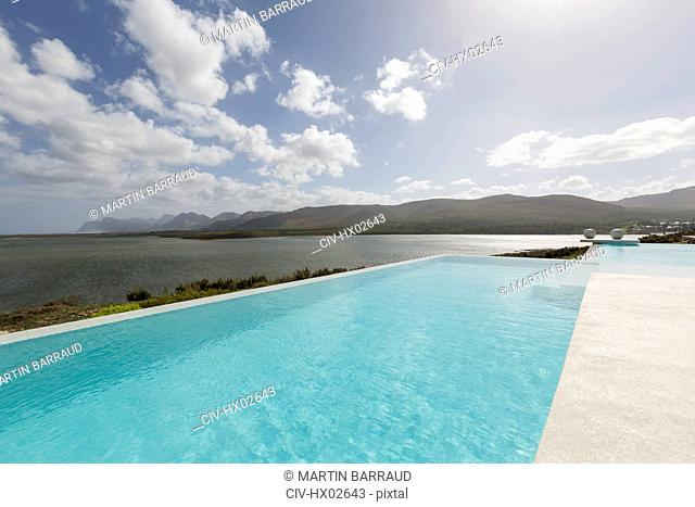 Sunny, tranquil infinity pool with ocean view