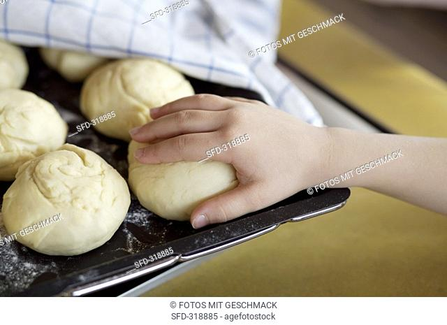 Child's hand reaching for an unbaked bread roll