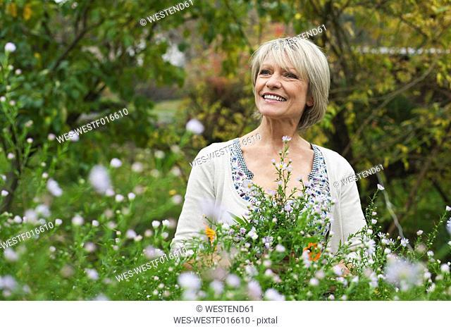Germany, Kratzeburg, Senior woman in garden, smiling