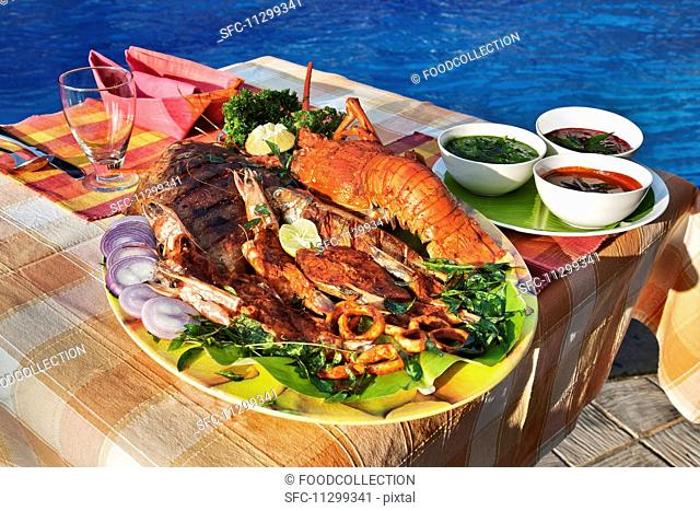 Spicy fish platter with lobster and various sauces (India)