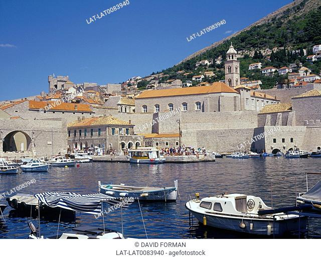 Harbour. View of old buildings. Red tiled roofs. Boats moored