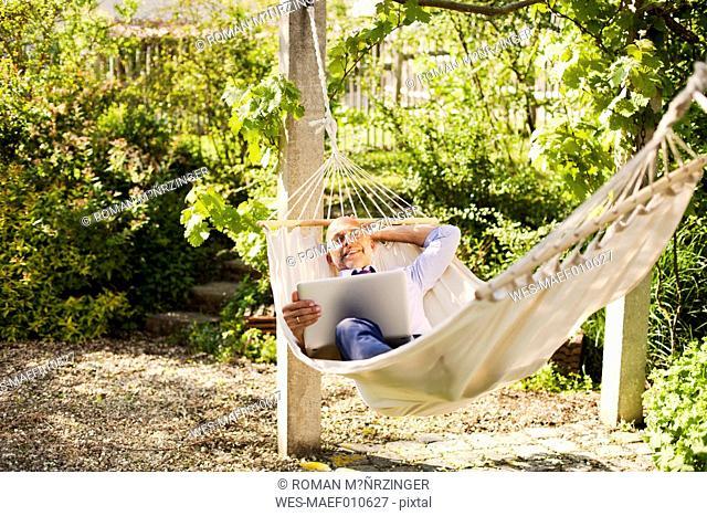 Businessman with laptop lying in hammock in a garden