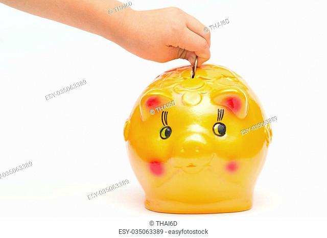 Children hand putting coins into a piggy bank