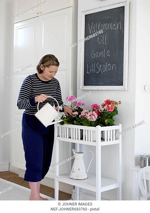 A woman watering flowers, Sweden