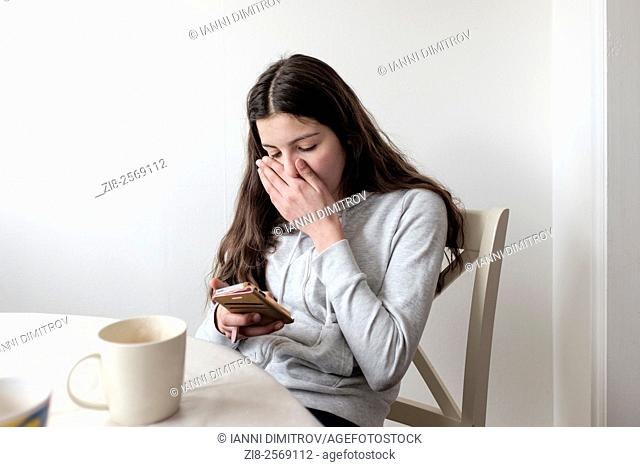 Teenage girl on her mobile phone,looking embarrassed