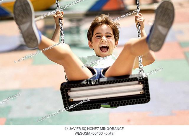 Portrait of screaming little girl having fun on a swing