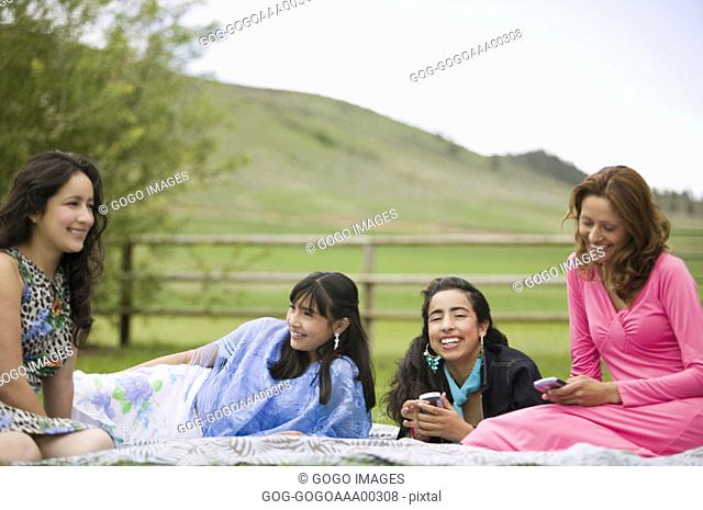 Woman and teenage girls 14-17 in park, smiling