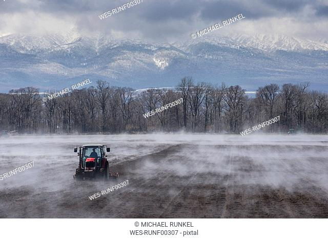 Hokkaido, Tractor seeding a field while it is vaporating from the warm ground