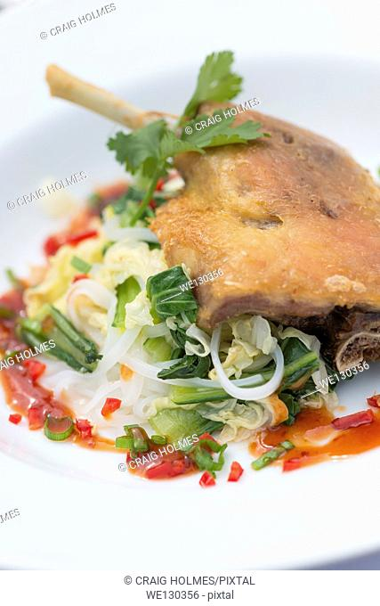 Leg of duck on a bed of vegetables and noodles