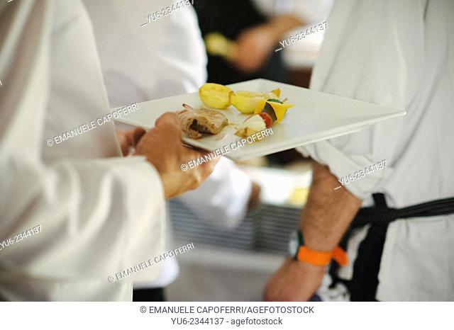 Waiter serves the second of meat and vegetables