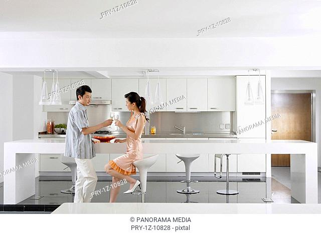 Young couple toasting at kitchen