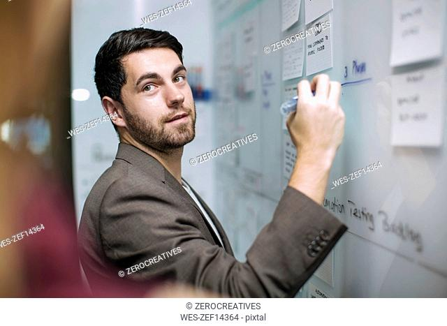 Businessman writing notes on a whiteboard