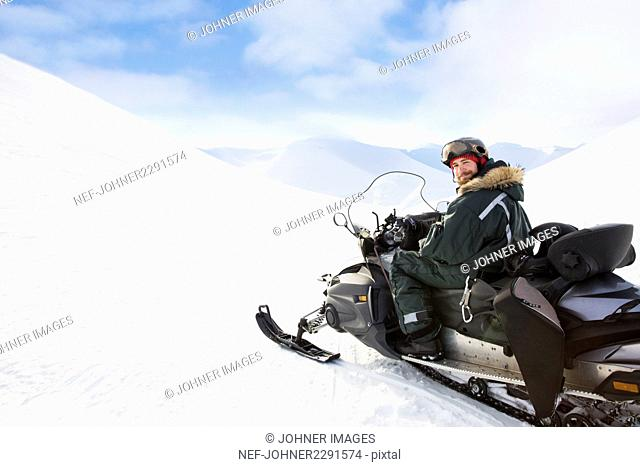 Man sitting on snowmobile