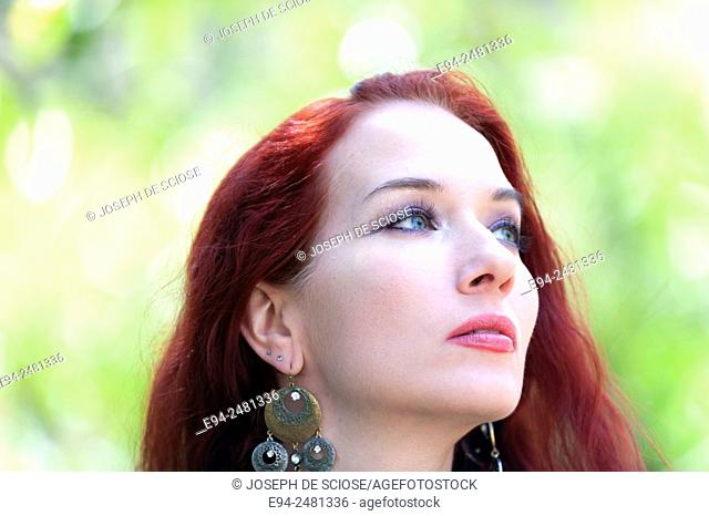 Portrait of a 37 year old redheaded woman looking way from the camera, outdoors