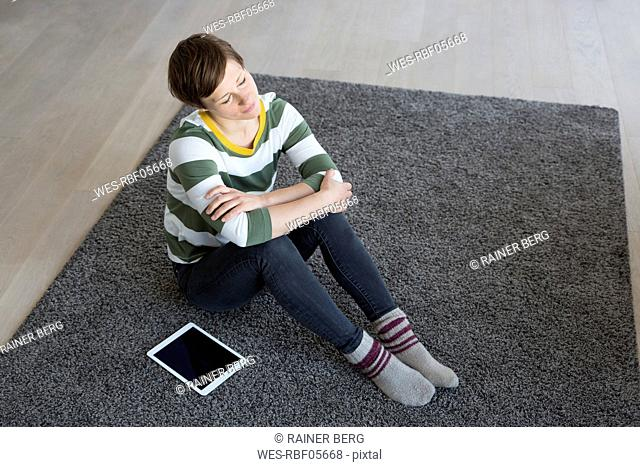 Woman with eyes closed sitting on the carpet in the living room