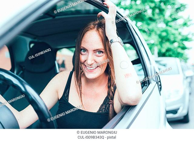 Portrait of young woman with long red hair and freckles at car window