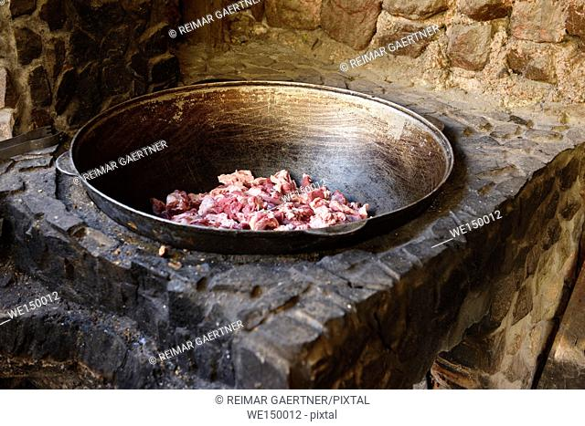 Outdoor stone cooking oven fit with raw lamb in steel bowl Turgen Kazakhstan