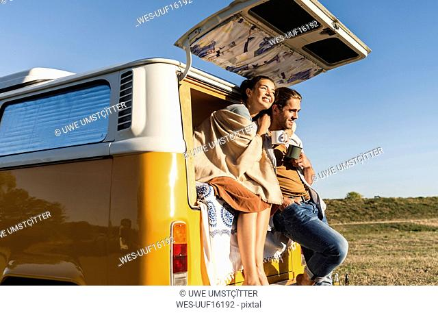 Happy couple doing a road trip with their camper, sitting on their bed, drinking coffee