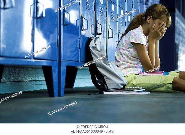 Female junior high student sitting on hall floor near lockers, upset and covering face with hands