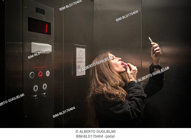Caucasian woman applying lipstick in elevator