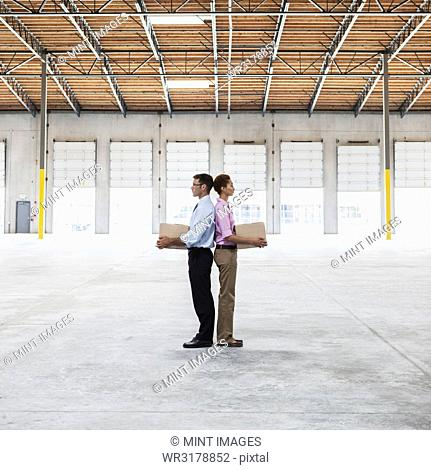 Caucasian man and black female holding cardboard boxes in middle of empty warehouse interior
