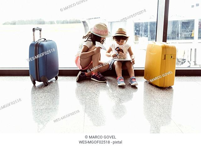 Two little girls waiting at airport, playing with digital tablet