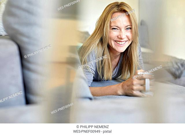 Laughing young woman relaxing on couch, drinking coffee